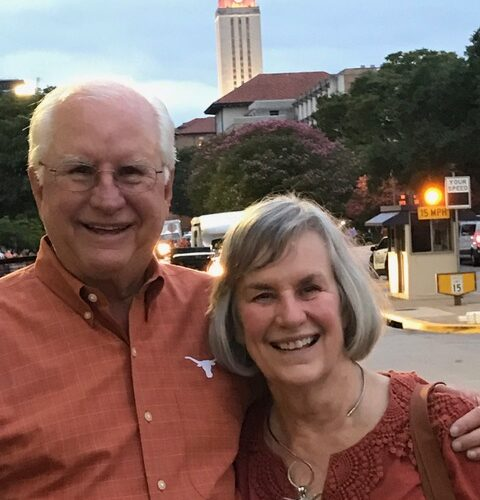 Longhorn couple Dudley and Judy Oldham pose on the UT campus with the UT Tower in the background