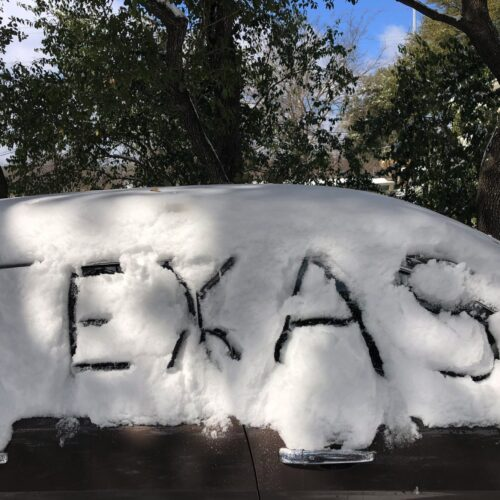 Image of. car covered in snow with the word Texas drawn in the snow, taken during Winter Storm Uri in February 2021.