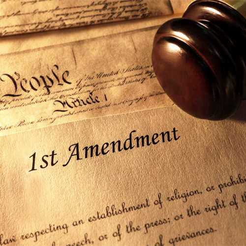 Copy of the 1st Amendment text on golden, aged paper with a gavel resting next to it.