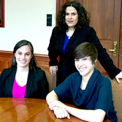 Children's Rights Clinic jury trial team sitting at a table. Student Attorney Brooke Ginsburg, Supervising Attorney Leslie Strauch and Student Attorney Rebeca Ojeda.