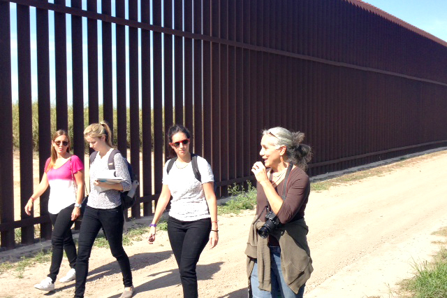 Clinic students, from left to right, Laura Schurr, Julia Furlong, and Ana Pecoraro walk with Dr. Margo Tamez (right) along the border wall.