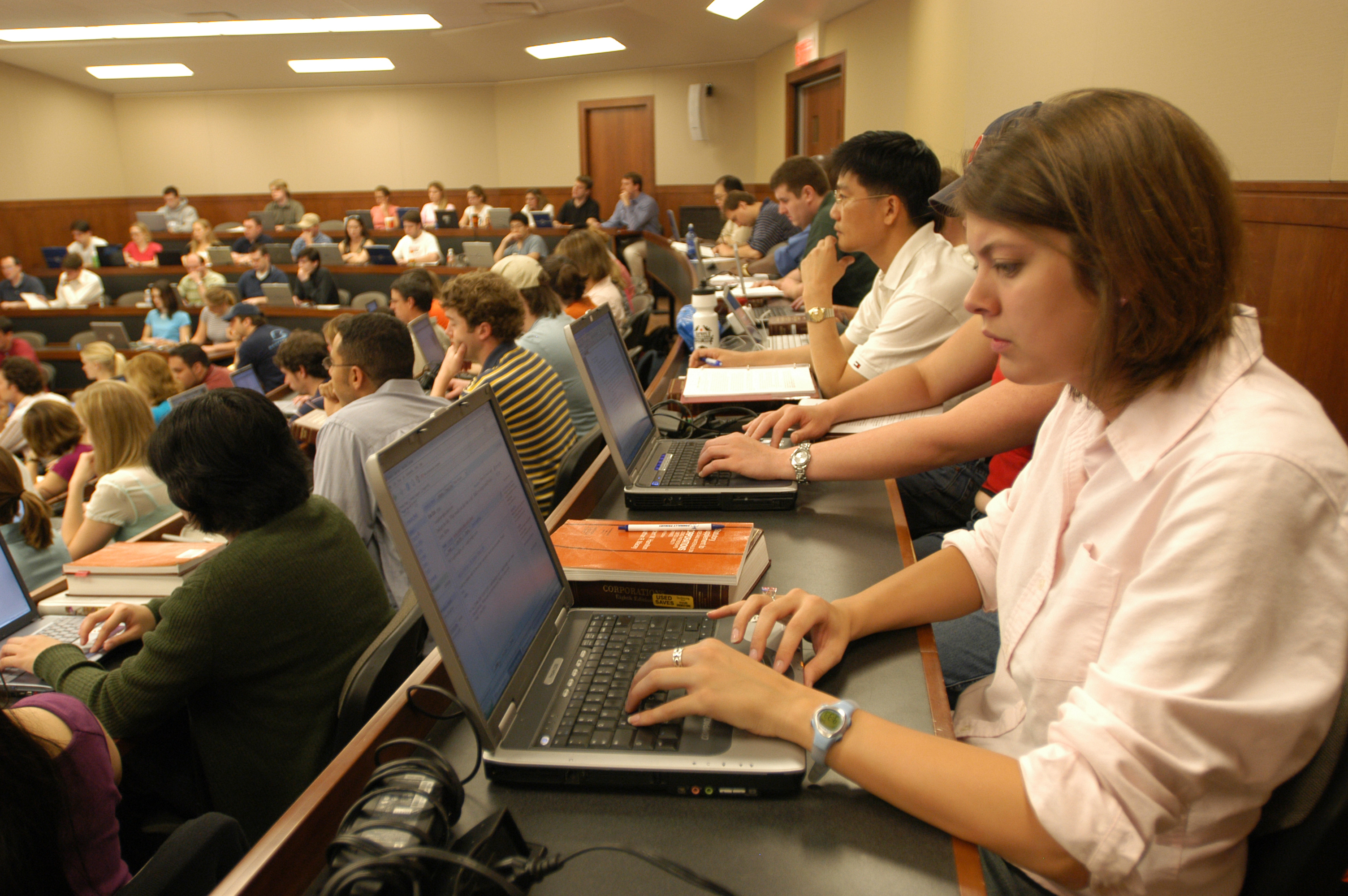Students on laptops attentive to a class lecture