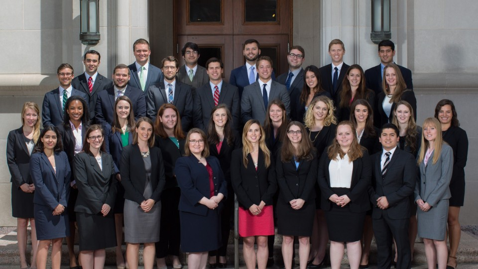The recent clerkship recipients in formal attire standing as a group on the steps of the University of Texas law school