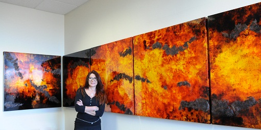 Artist Mery Godigna Collet poses with panels from her piece, Pure Energy. Photo by Steph Swope.