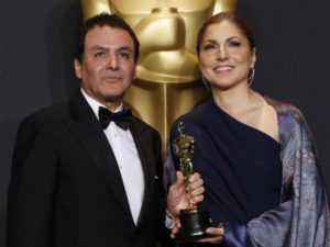 man and woman holding Oscar award
