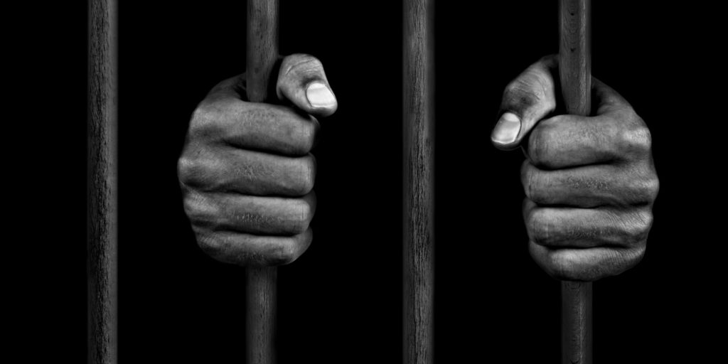 hands of an African-American holding onto jail bars