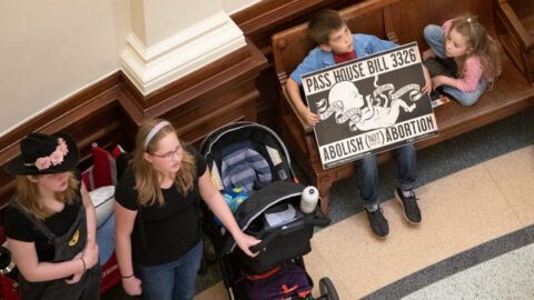 Anti-abortion advocates in a building, with a young boy holding a poster of a fetus.