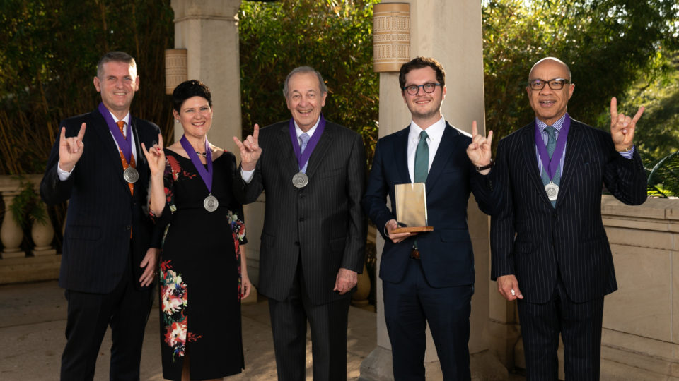 All the 2019 Alumni Award Winners, standing with their hands up in the