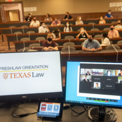 Two computer screens, one showing a Zoom screen, and one showing the Freshlaw Orientation slide, in a room full of students at orientation.