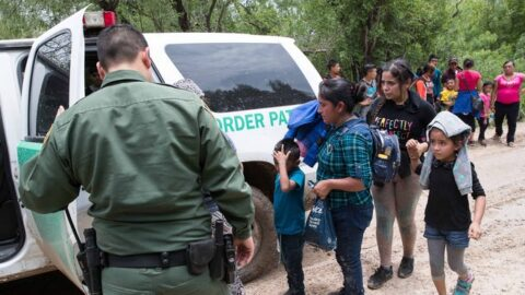 Border Patrol agents take a group of migrant families to a safer place to be transported after intercepting them near McAllen, Texas