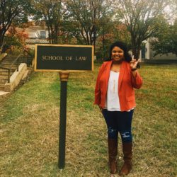 """Amber Magee wearing an orange jacket, holding up the 'hook em' emblem, in front of the """"School of Law"""" sign"""