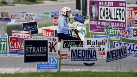 Woman drives a motor scooter past dozens of campaign signs