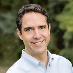 Professor Chesney in an open collar blue button-down shirt