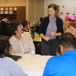 Eva Sikes standing and speaking to five students seated at a table during Pro Bono in January 2020.