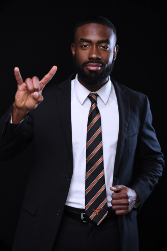 Photograph of Anthony Collier is a dark suit and striped tie and flashing a Hook 'em Horns hand sign