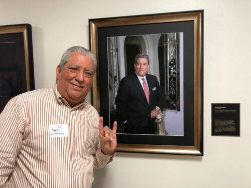 Bob estrada poses with his alumni portrait at the law school, fishing the Hook 'em sign.