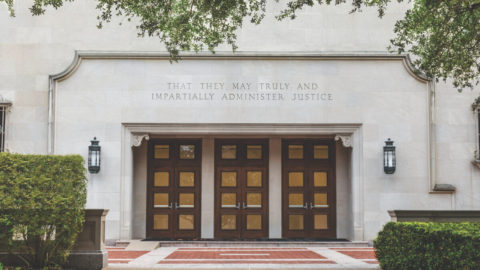 "The exterior doors of Townes Hall at the University of Texas School of Law, with an inscription chiseled above: ""That they may truly and impartially administer justice."""