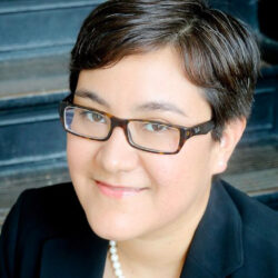 A portrait of Frances Valdez, in a black blazer and pearl necklace and glasses.