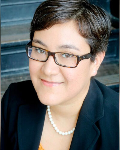 A portrait of Frances Valdez, in a black blazer and pearl necklace and glasses, the executive director of Houston in Action.