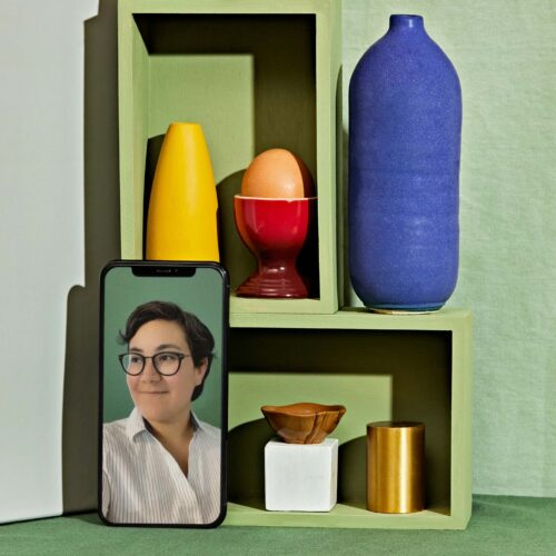 A photo collage depicts stacked green boxes against a green background with different colored objects inside. Resting against one of the boxes is an iPhone that has a portrait of Frances Valdez. She is wearing a striped top and glasses.