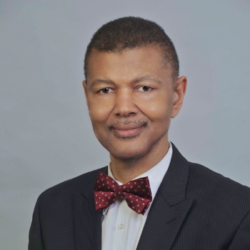 Portrait of Gary Bledsoe, wearing a black jacket and a red bow tie with white polka dots.