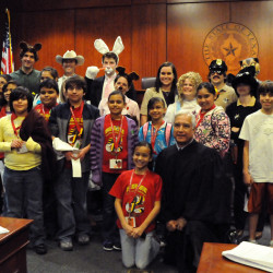 "Judge Edward Prado, '72, and costumed Law School students with schoolchildren who watched a mock trial of ""Gold E. Locks"" during the 2010 Explore UT."