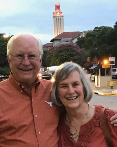 A couple poses on the UT Austin campus with the landmark UT Tower in the background.