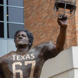 Statue of Julius Whittier from the front, wearing a Texas football jersey with the numbers 67 on front, holding his helmet in the air in his left hand.