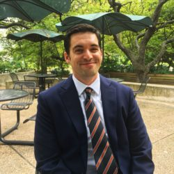 Dustin Farahnak, pictured in front of picnic benches and trees at The School of Law