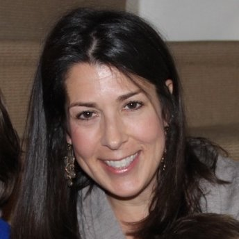Woman with long, straight, brown hair smiles at the camera