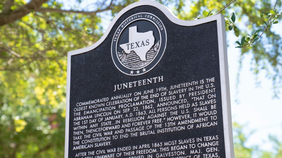 A large metal sign explaining Juneteenth's history in front of trees.