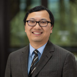 Portrait of Lei Zhang, wearing glasses and a blue shirt with a gray jacket and striped tie.