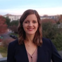Portrait of Caitlin Machell Pevey, pictured in front of fall-colored trees