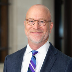 Portrait of The Honorable Robert Pitman, who is wearing glasses and a blue, purple, and white striped tie.