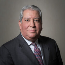 Portrait of Robert Estrada, wearing a black jacket and a red and black tie.