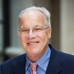 Portrait of Prof. John A. Robertson, wearing glasses, a blue shirt and jacket with a peach tie.