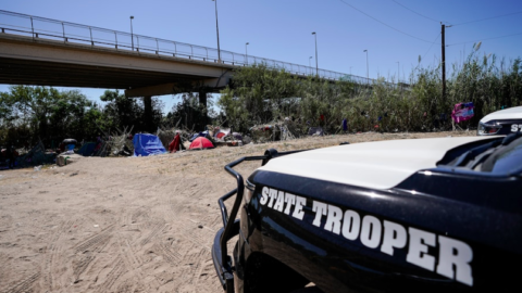 A State trooper car near migrant tents