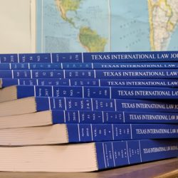 A stack of the blue Texas International Law Journal books, with a world map hanging on the wall behind them