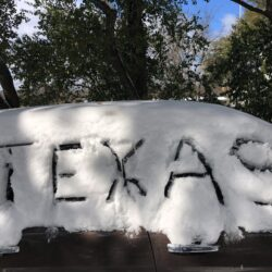 "A car covered in snow with the word ""Texas"" drawn in the snow, taken during Winter Storm Uri in February 2021"
