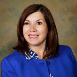 Headshot of Betty Balli Torres, wearing a bright blue jacket