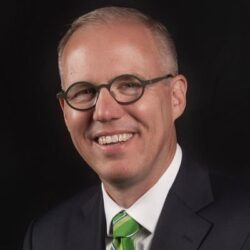 Portrait of Taylor, Texas Mayor Brandt Rydell wearing glasses and a green tie.