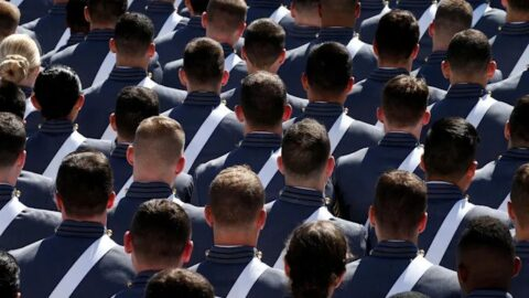 Image of West Point cadets standing in formation, facing away from the camera.