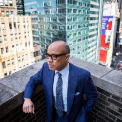 Darren Walker, wearing a blue suit, standing on a balcony in New York City