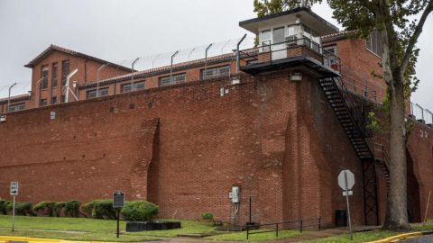 The exterior of a red brick prison