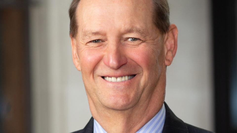 Portrait of Professor Erben, wearing a bright orange tie