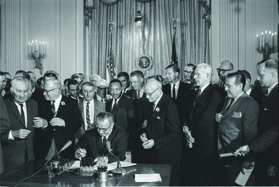 Lyndon B. Johnson, the 36th president of the United States, signs into law the Civil Rights Act in 1964 as Martin Luther King Jr. and others look on. Photo courtesy of LBJ Library