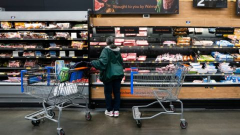 A woman pushes a shopping cart and looks at the selection in the meat section of a grocery store