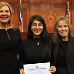 The Honorable Brandy Mueller, Travis County Court at Law #6, with award recipient Noorulanne Jan, '21 and The Honorable Orlinda Naranjo standing in a courtroom