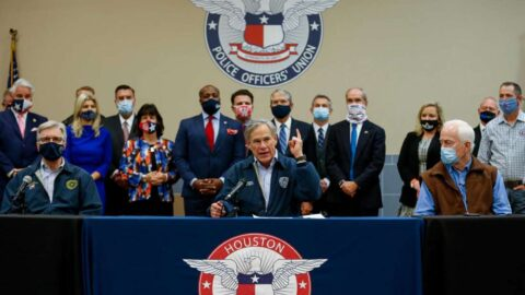 """Gov. Greg Abbott, sitting in the center of a large table, talks to reporters during a press conference inside the Houston Police Officer's Union Headquarters, where he signed a """"back the blue"""" pledge. Surrounding him are individuals wearing masks."""