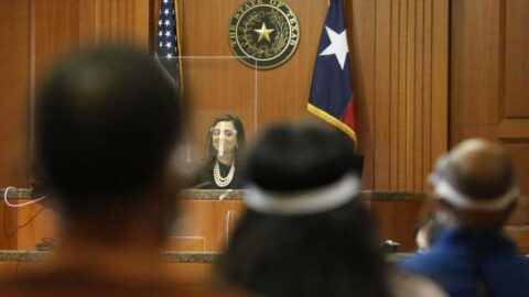 Harris County Judge Rabeea Sultan Collier wears a face shield and sits behind a plexiglass wall as the jurors sit in the gallery during a jury trial in the 113th court
